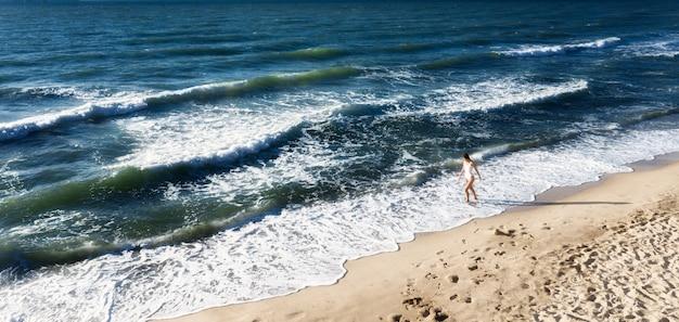 Молодая женщина гуляет на пляже вдоль береговой линии с голубой водой