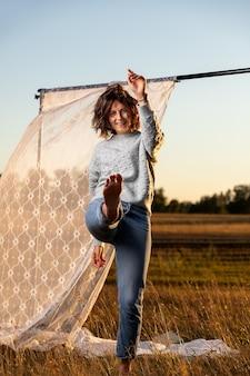 白いカーテンの横にあるフィールドの上を歩く若い女性