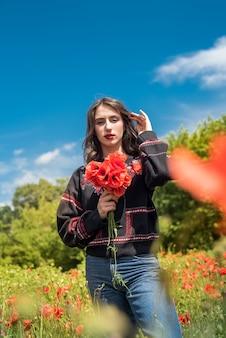 여름 시간에 빨간 양 귀 비 필드에 걷는 젊은 여성
