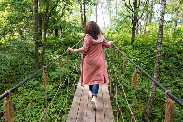 Молодая женщина, идущая по подвесному мосту в лесу. путешественник на веревочном мосту. женщина путешествия на концепции отпуска. походы, летние занятия на свежем воздухе.