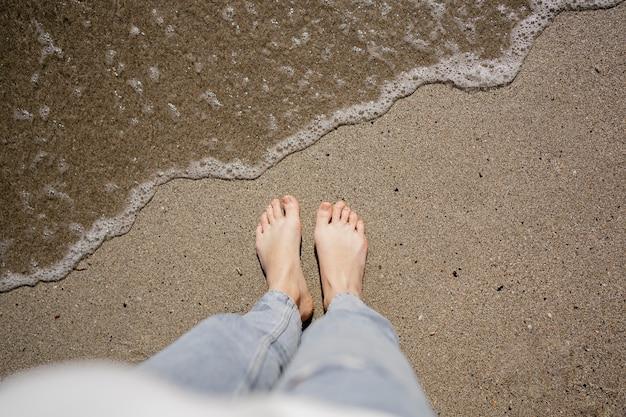 ビーチの砂の上を歩く若い女性