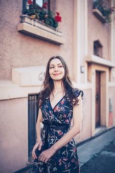 誰かを見て、笑顔で通りを歩いている若い女性