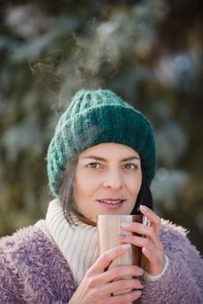 Молодая женщина гуляя на зимний день, держа кружку нержавеющей стали перемещения с горячим кофе. многоразовая бутылка для воды.