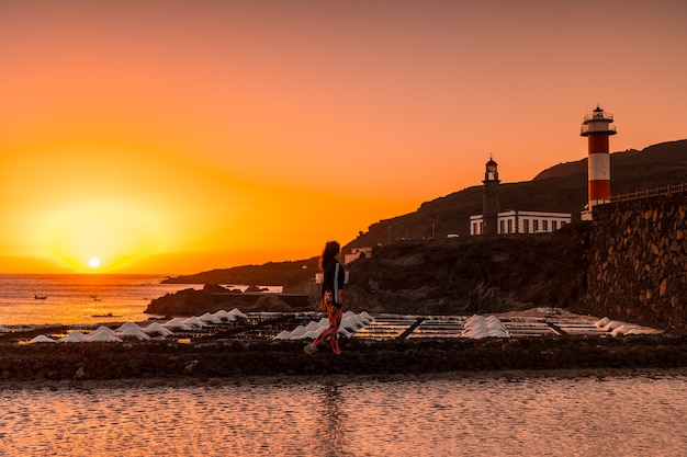 A young woman walking in the orange sunset in the salina and in the background the fuencaliente lighthouse on the route of the volcanoes south of the island of la palma, canary islands, spain