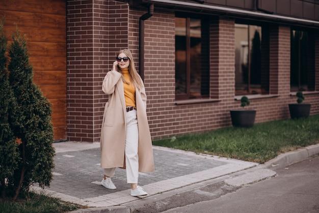 Giovane donna che cammina fuori di casa