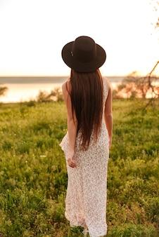 모자를 쓰고 필드에 야외에서 걷는 젊은 여성.