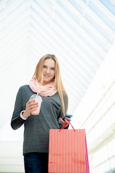 Young woman walking in shopping mall making a call with smartphone holding bags and a drink