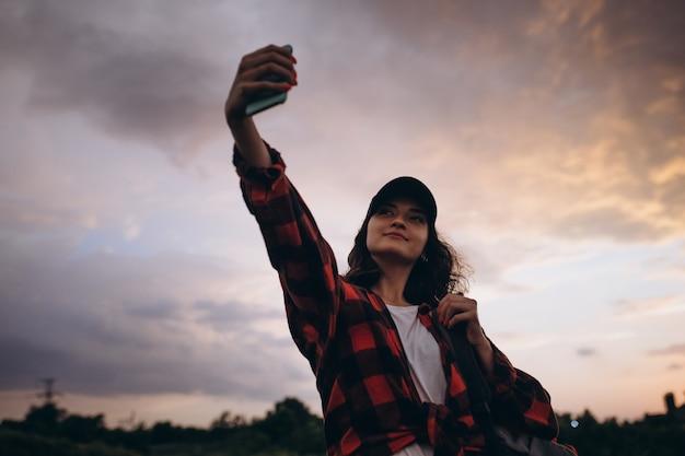 Молодая женщина гуляет, гуляет, делает селфи в летнем лесу