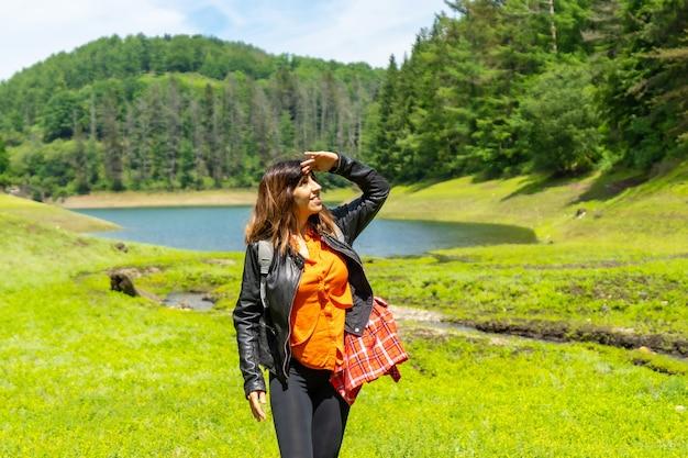 湖と松林のある畑を歩く若い女性