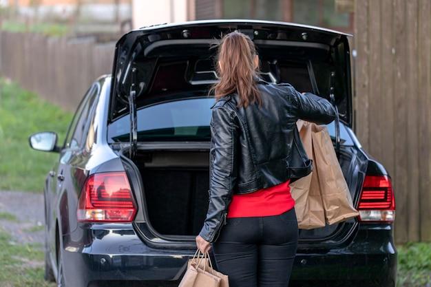 Молодая женщина идет к машине с покупками на рынке