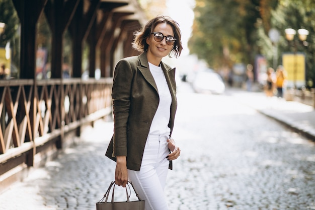 Young woman walking in town in sunglasses