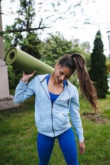 Giovane donna che cammina nel parco urbano tenendo il tappeto fitness.