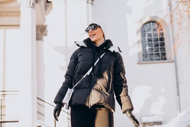Giovane donna che cammina all'orario invernale