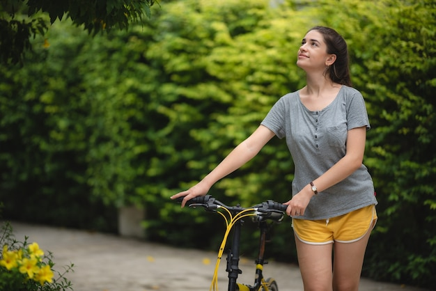 公園で自転車で歩く若い女性