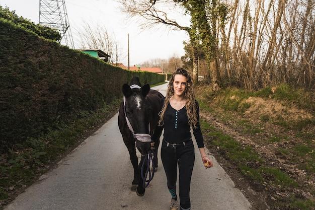 Молодая женщина гуляет с лошадью через конноспортивный комплекс