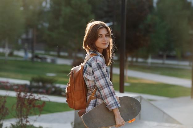아침에 공원에서 스케이트보드를 들고 걷는 젊은 여자