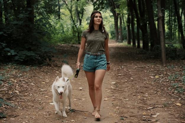白いハスキーと歩く若い女性