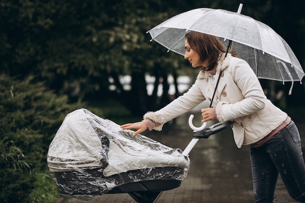 Young woman walking with baby carriage under the umbrella in a raint weather