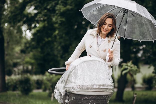 雨の日の傘の下でベビーカーと一緒に歩いている若い女性