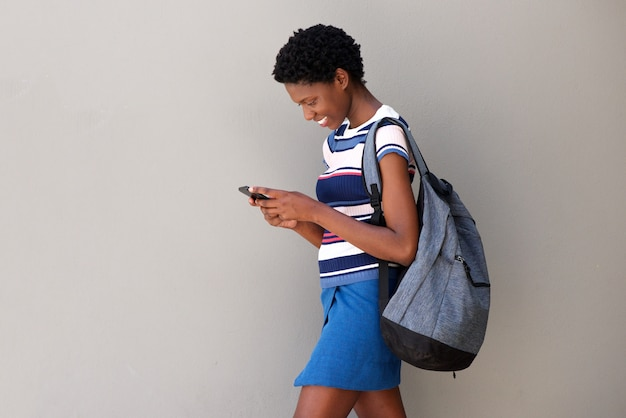 Young woman walking with bag and using smart phone on gray background