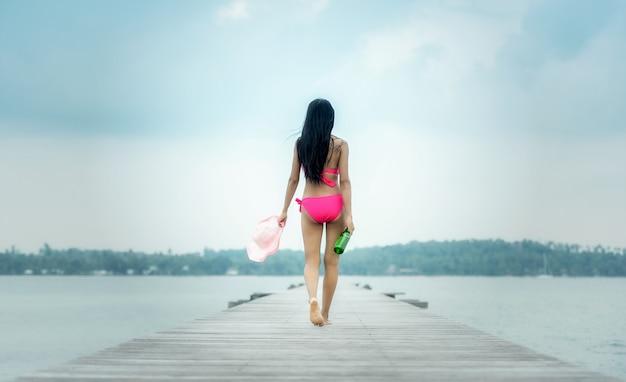 桟橋、遠隔の熱帯のビーチおよび国にビール瓶を持って歩く若い女性。