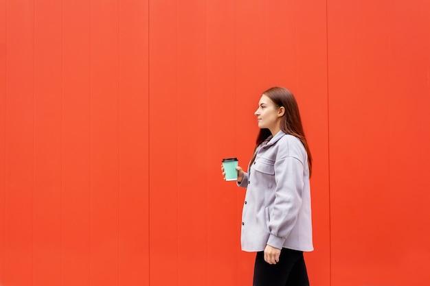 커피 한 잔을 들고 걷는 젊은 여성