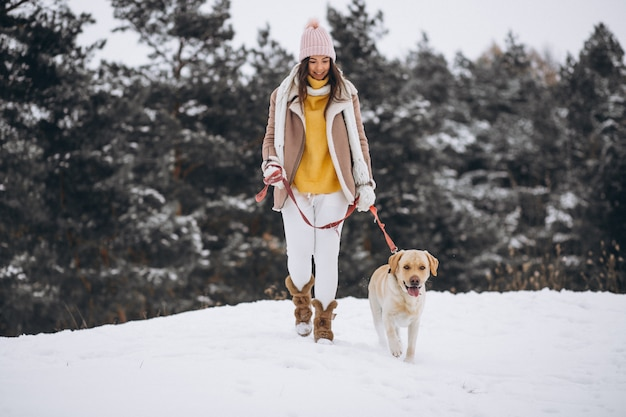 Молодая женщина гуляет с собакой в зимнем парке
