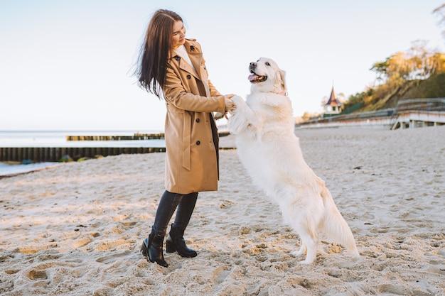 Молодая женщина гуляет со своим питомцем золотистый ретривер на берегу моря. собака держится на двух лапах.