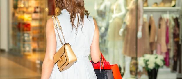Молодая женщина, ходьба с хозяйственными сумками