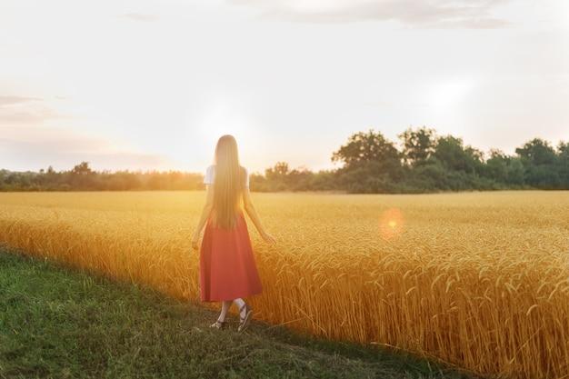 若い女性は麦畑に沿って歩きます。緑の草と熟した耳のコントラスト。