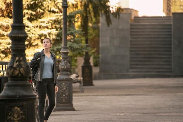 Молодая женщина гуляет по городу. портрет в полный рост снаружи. туристическое путешествие по старинным дворам.