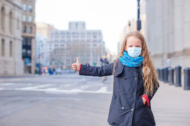 Young woman walks in empty new york in a mask protecting from the virus
