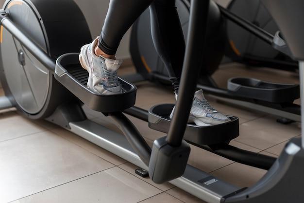 젊은 여자는 체육관에서 스테퍼 시뮬레이터에 운동복에 산책