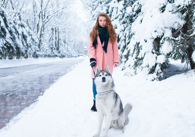 Молодая женщина гуляет в парке с сибирским хаски