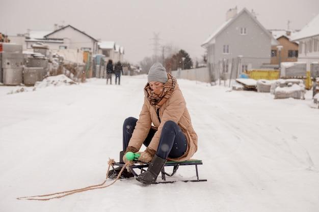 若い女性は冬の森を歩きます。暖かい冬の服を着ている美しい若い女性