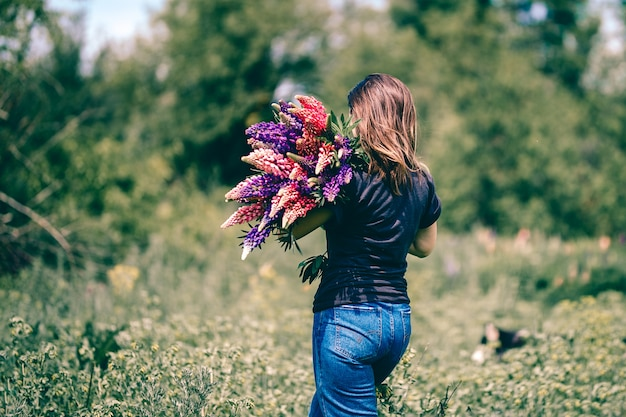 A young woman walks in the meadow with a bouquet of lupins in hand