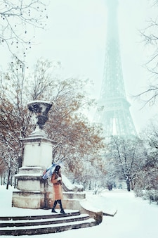 A young woman walks in a snowy winter paris against the eiffel tower