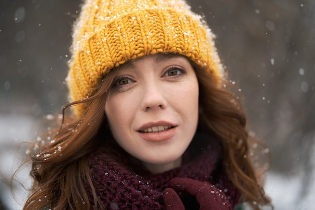 A young woman walks in a sunny snowy city. she wears a faux fur coat, yellow knitted hat and scarf. she is very happy.