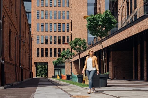 若い女性は春の日に街の通りを歩きます。都市景観。人生は素晴らしい。観光と喜び。旅行についてのブログ。ヨーロッパの都市。充実した生活を送る能力。