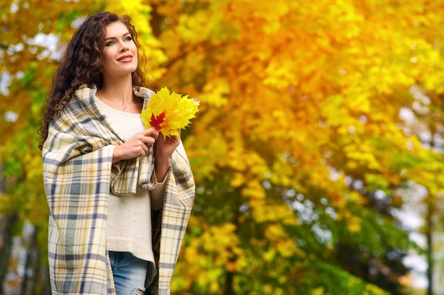 젊은 여자가 가을 공원을 산책하고 담요에 싸여 노란색 빨간색 녹색 잎을 수집