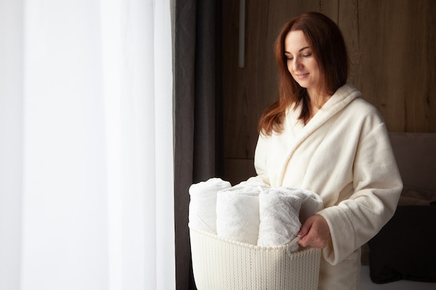 Young woman in warm bathrobe is standing near window and holding basket of rolled up white towels. breeze of freshness from washed linen. natural textile. spick and span concept. well ordered.