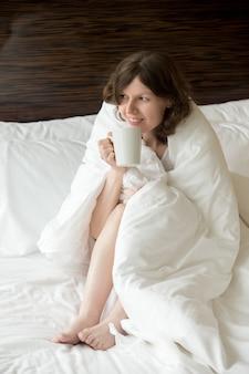 Giovane donna sotto coperta calda