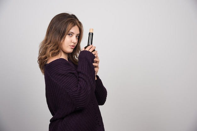 Young woman in warm knitted sweater holding a bottle of wine .