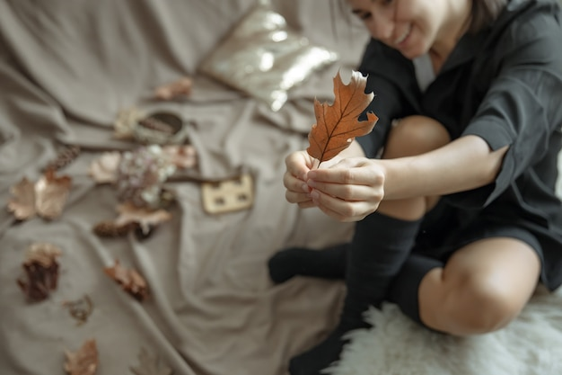 A young woman in warm stockings at home holds an autumn leaf in her hands, blurred background.