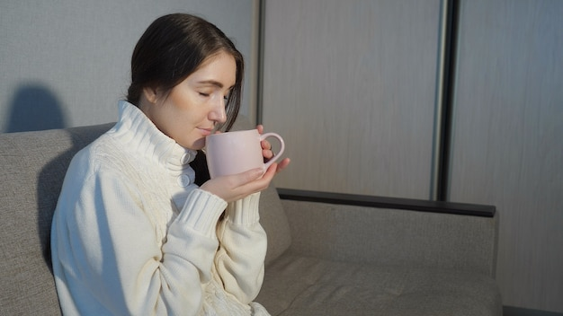 Young woman in warm sweater sitting on sofa and and drinking tea at home.