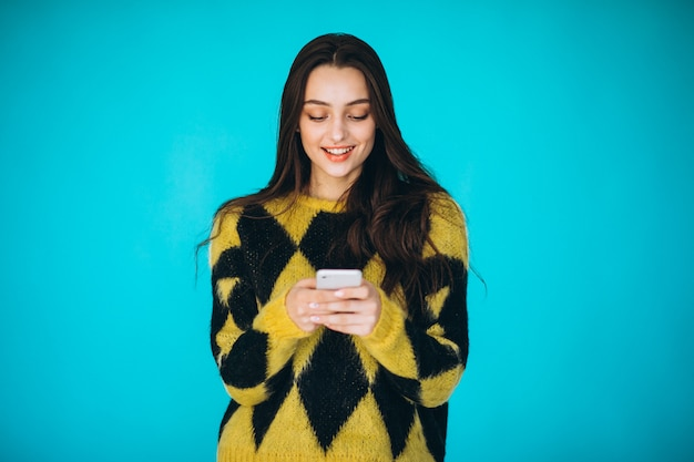 Young woman in a warm sweater using phone