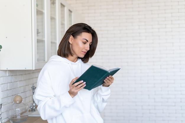 La giovane donna in una calda felpa con cappuccio bianca a casa in cucina legge un libro al mattino
