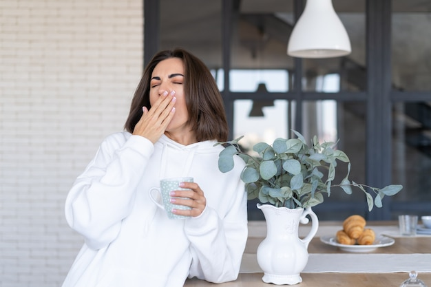 Young woman in a warm white hoodie at home in the kitchen, starts her day with a cup of coffee