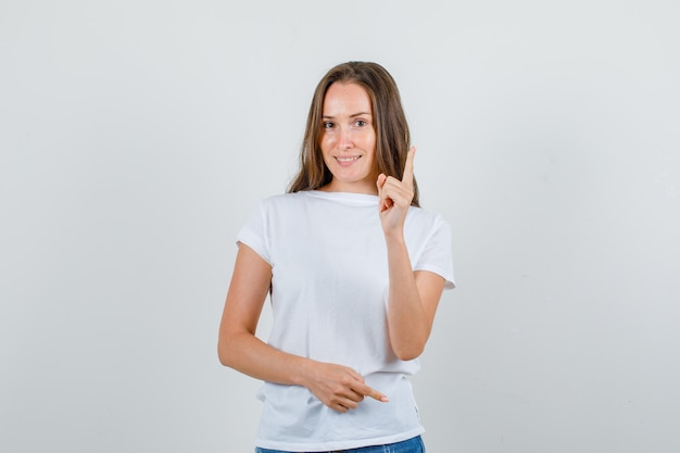 Young woman warning somebody with finger gesture in white t-shirt, shorts front view.