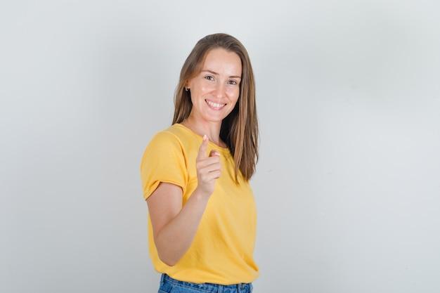 黄色のtシャツで楽しみのために指で警告し、陽気に見える若い女性